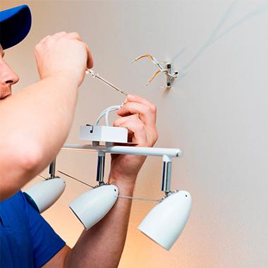 Elettricista professionista della bottega di quartiere che monta una lampada